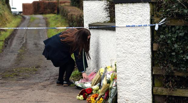 A woman laying flowers at the scene in January