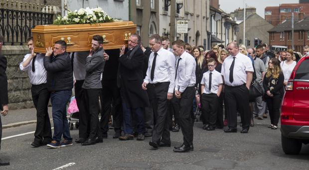 Mourners carry the coffin of Toirdealbhach Larkin in Newry yesterday