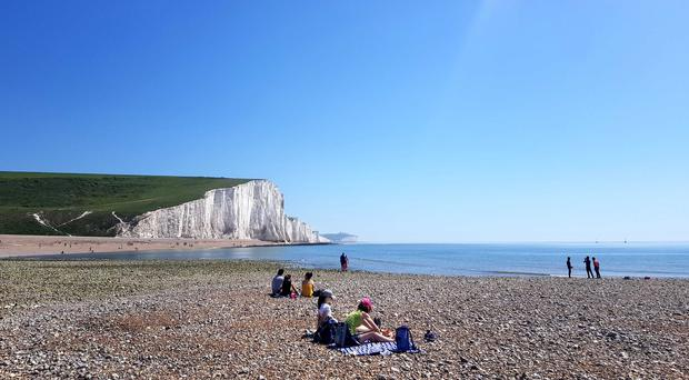 People enjoy the weather on the beach beside the Seven Sisters Cliffs in Sussex (Catherine Wylie/PA)