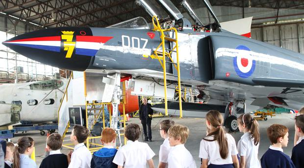 Pupils from St Ita's Primary School, Belfast, look at the Phantom jet on display at the Ulster Aviation Society at the Maze