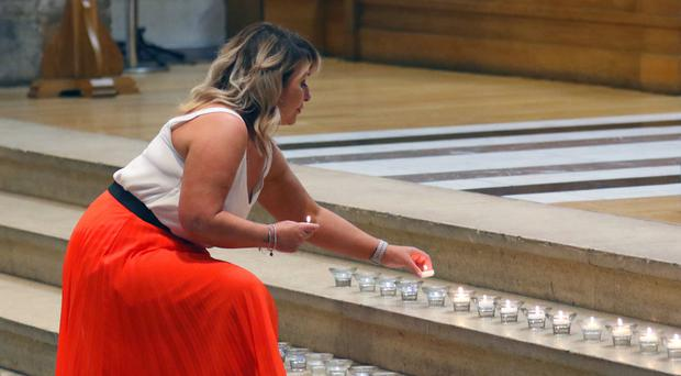 Women lay candles during the Saying Goodbye service at St Anne's Cathedral