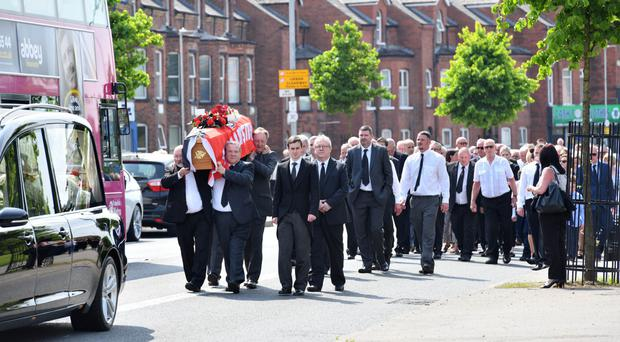 The funeral of Crusaders secretary Harry Davison walks along the Shore Road and past Seaview football ground