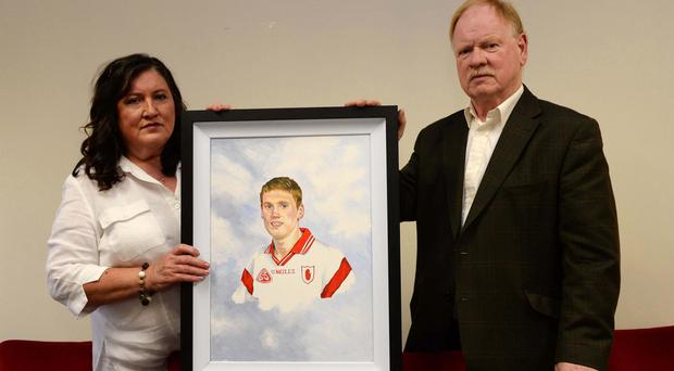 Brendan and Bridget McAnallen with a portrait of their son Cormac, who passed away suddenly at home from Sudden Arrhythmic Death Syndrome in 2004