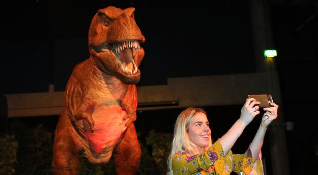Katie Smith takes a selfie beside a Tyrannosaurus rex on display at the new dinosaur exhibition at W5