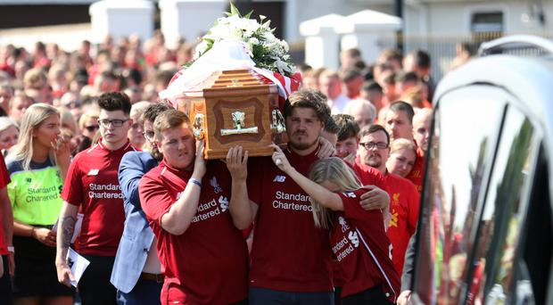 Family and friends wearing Liverpool tops carry the coffin of Robbie Fleming, a fan of the football team, in Lisburn