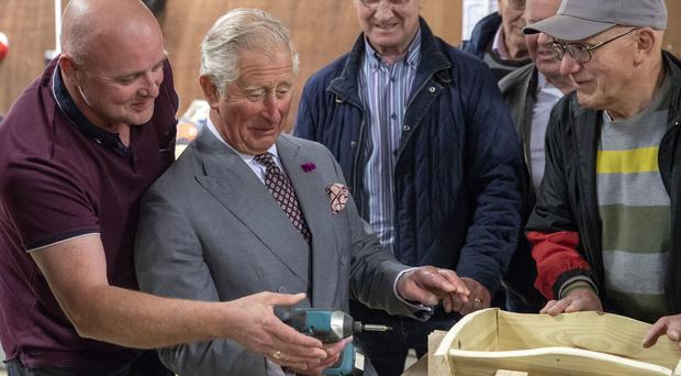 The Prince of Wales uses a power drill to secure a wheelbarrow during a visit to the Owenkillew Community Centre (Steve Parsons/PA)