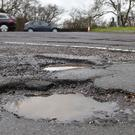 A car passes potholes in a road near Peterborough (PA)