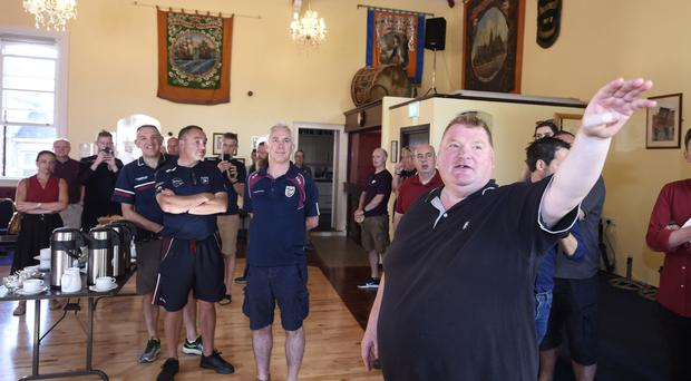 Ballynafeigh district master Noel Ligget shows his guests from Bredagh GAC around the hall