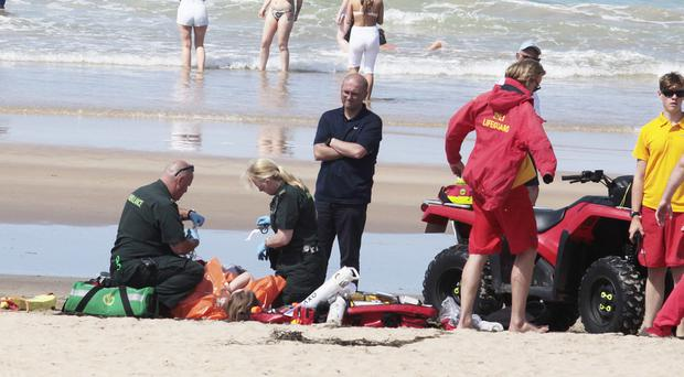 Lifeguards and paramedics attend to a young girl after she was rescued at East Strand Beach in Portrush yesterday