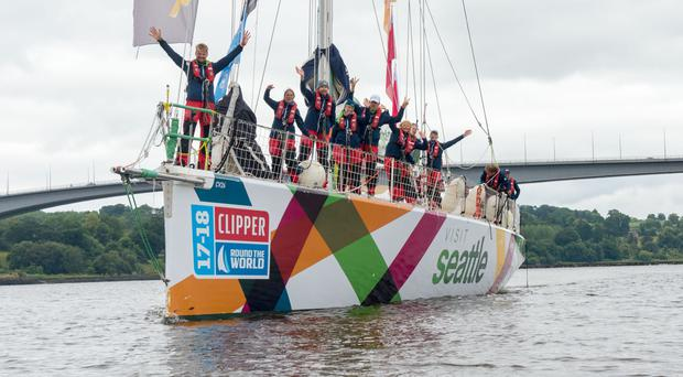 The crew of Visit Seattle celebrate as they arrive under the Foyle Bridge in first place