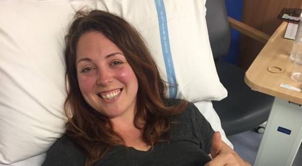 Adrianne Peltz giving the thumbs-up from her hospital bed
