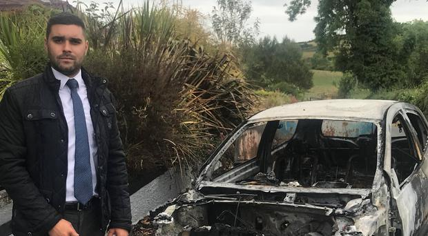 Alan Lewis of the UUP beside the car damaged in the arson attack