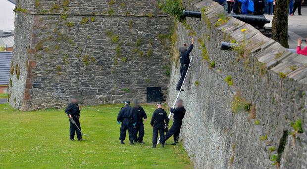 PSNI officers examine a section of Derry's Walls yesterday for embedded bullets after six shots were fired at officers