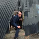 Simon Coveney examines damage in the Bogside during visit
