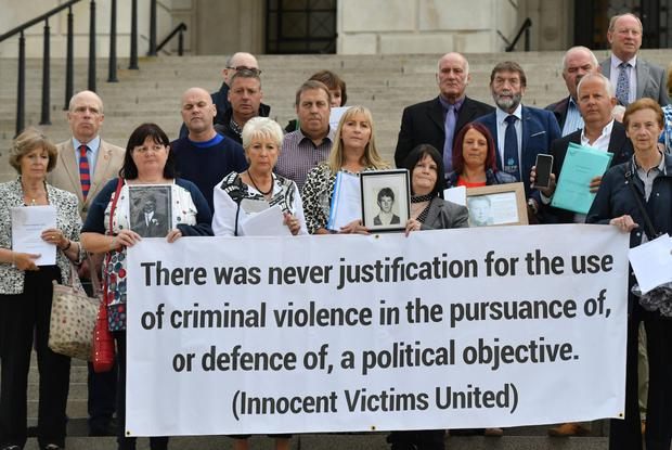 Campaigners on the steps of Stormont holding HET reports and pictures of their loved ones during an event held in Belfast last night
