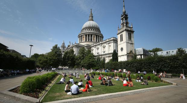 People sitting in the sun in St Paul's Cathedral Churchyard Gardens in London last weekend (Jonathan Brady/PA)
