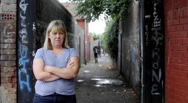 Resident Angela Whelan in an alley in the Westrock Gardens area where a man was shot in both legs on Saturday