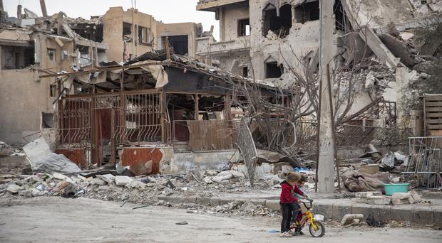 Children riding a bicycle next to destroyed buildings in Raqqa, Syria (Amnesty International/PA)