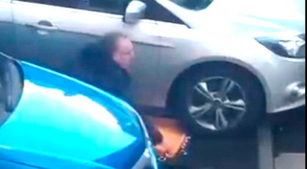 An image shows Sinn Fein MLA Gerry Kelly appearing to remove a car wheel clamp