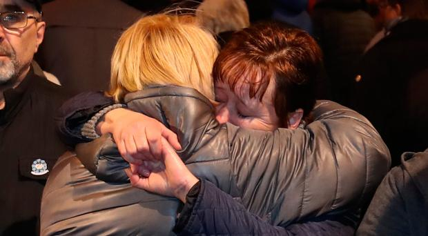 Michelle Williamson, whose mother and father died in the bomb, is comforted during a memorial march in Belfast to mark the 25th anniversary of the atrocity in which nine innocent people were killed by an IRA bomb