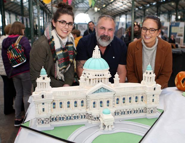 Shannon More, John Holliday and Lauren Quee with Belfast City Hall by the French Village Bakery