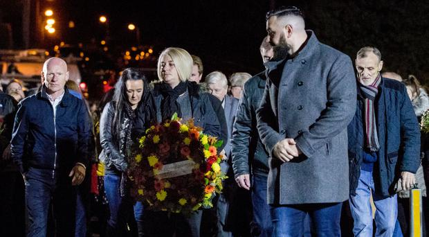 John Burns' daughter Gillian holds a wreath, as seven other members of the Greysteel massacre families look on during a vigil to commemorate the 25th anniversary of eight people being murdered on October 30, 1993 by members of the UFF