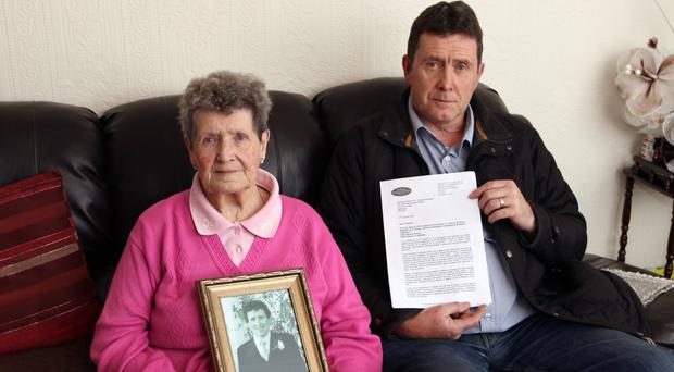 Beatrice Worton and her son Colin holding a photograph of murdered Kenneth and a copy of the letter received from the Public Prosecution Service