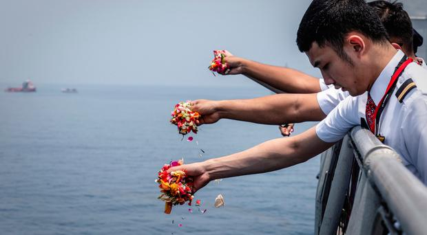 Colleagues of the doomed Lion Air flight crew throw flowers into the sea