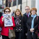 Irish Senator's Mark Daly of Fianna Fail (left), Independent Frances Black (2nd from left), Frank Feighan of Fine Geal (3rd from right), with members of the families of those killed during the Ballymurphy massacre stand with images of those killed, outside Laganside Courts in Belfast (Liam McBurney/PA)