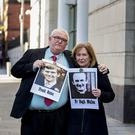 Pat Quinn (left) holds an image of his brother, Frank Quinn, with his arm around Geraldine McGrattan, who holds an image of her uncle Father Hugh McMullan (Liam McBurney/PA)
