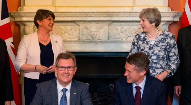 Prime Minister Theresa May stands with DUP leader Arlene Foster as DUP MP Sir Jeffrey Donaldson signs the paperwork in June 2017 with the then Parliamentary Secretary to the Treasury, Gavin Williamson, to cement the party's confidence and supply deal to support Mrs May's minority Conservative government in Commons votes