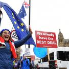 An anti-Brexit campaigner waves at passing vehicles in Old Palace Yard, Westminster. (Kirsty O'Connor/PA)