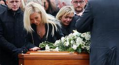 Laura Donegan touches the coffin of her husband Jim Donegan