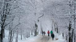 People stroll through the snow-covered landscape in Oberwiesenthal, Germany