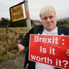 Boris Johnson lookalike Drew Galdron, who styles himself as Faux Bojo, stands on the Irish border (Niall Carson/PA)