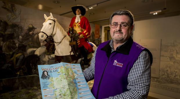 Dr Jonathan Mattison, curator of the Museum of Orange Heritage in Belfast pictured with a copy of the Williamite Trail (Liam McBurney/PA)