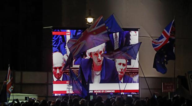 People watch Prime Minister Theresa May speak on a large screen (Steve Parsons/PA)