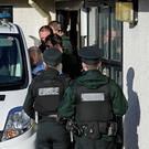 Officers arrest a man and place him in a police van at Craigavon Area Hospital following the incident yesterday morning