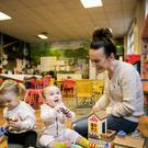Claire Magill watches her daughters Thea (left) and Avery at the Donegall Road Methodist Complex, Belfast, run by Southcity Resource and Development Centre (Liam McBurney/PA)