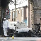 Forensic investigators at the scene of the car bomb blast (Niall Carson/PA)