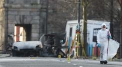 Forensic investigators at the scene of the bomb blast on Bishop Street (Niall Carson/PA)