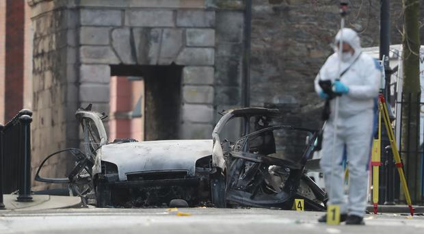 Forensic investigators at the scene of a car bomb blast on Bishop Street in Londonderry (Niall Carson/PA)