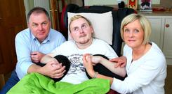 Declan McMullan, who has locked-in syndrome, with his dad John and mum Brenda at their home
