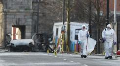 Forensic investigators at the scene of a car bomb blast on Bishop Street (Niall Carson/PA)