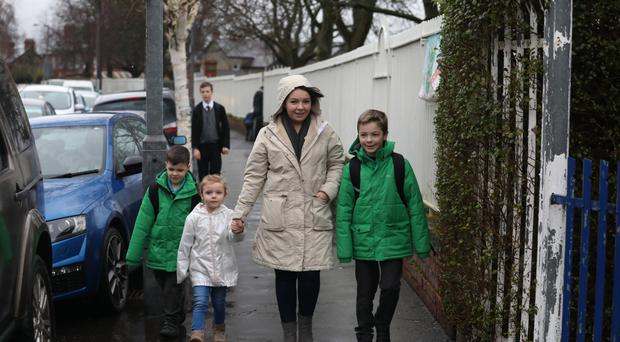 Kylie King walks home from school with her three children, William, (10), Ryan, (8), and Annie (5). Pic by Peter Morrison