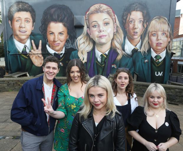 Derry Girls creator Lisa McGee (second from left) with cast members visiting the Derry mural by UV Arts.