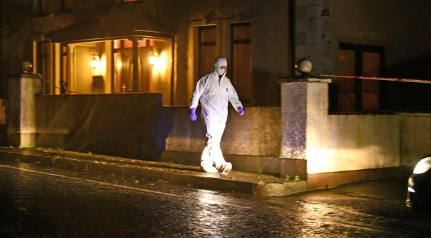 A forensic officer at the house in Glenwherry, Co Antrim, last night