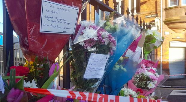 Messages and floral tributes left near the scene in east Belfast where community worker Ian Ogle died (PA)