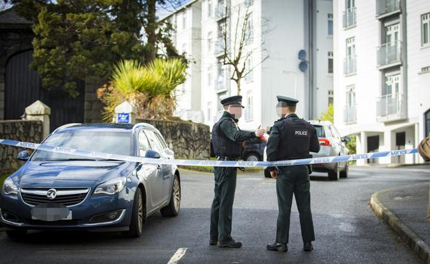 Police at Glin Ree Court after three bodies were found in a flat