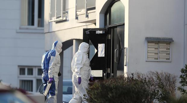 Forensic officers at flats in Newry where the bodies were found (Niall Carson/PA)